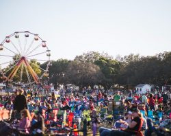 Runaway Country Music Fest, crowd sits on lawn chairs in field with ferris wheel behind