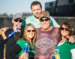 Runaway Country Music Fest, three men and two women in green hug & smile with drinks